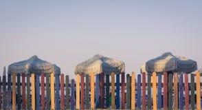 Cerca colorida na praia com guarda-chuvas retros Estilo da cor de tom do vintage Imagem de Stock Royalty Free