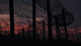 A cerca com arame farpado e grama no fundo de um céu vermelho-azul nebuloso vídeos de arquivo