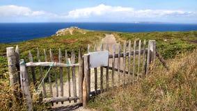 Cerca con un camino arenoso que lleva al océano imagen de archivo