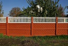 Cerca concreta branca vermelha rural na grama na rua fotografia de stock royalty free