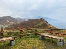 Cerca da montanha, banco da cadeira, mar, grama verde e nuvem Fotos de Stock