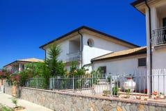 Cerca das casas de campo de dois andares brancas com jardim Imagem de Stock