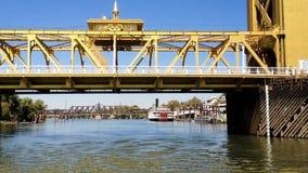 Cerca de acercamiento al puente de la torre de Sacramento del barco en el río metrajes