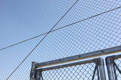 Cerca de alambre de metal con el cielo azul fotografía de archivo