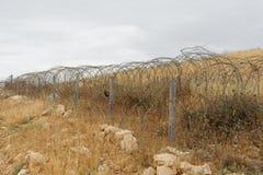 Cerca de alambre de púas de la cinta o de la maquinilla de afeitar a través de la colina del desierto en día nublado Fotografía de archivo