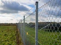 Cerca de chainlink larga del metal que asegura la granja solar o fotovoltaica del panel con el cielo nublado dramático en Alemani Fotografía de archivo