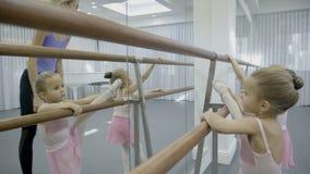 Cerca de la máquina de madera del ballet, aprenda el profesor y a los niños jovenes almacen de video