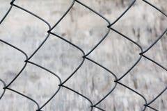Cerca de la malla metálica en un fondo gris imagen de archivo