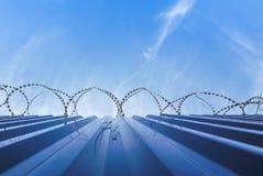 Cerca de la protección de Barbwire con el cielo azul Fotografía de archivo