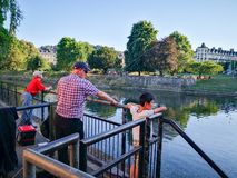 Cerca de Londres el río Támesis y del puente de Putney, dos viejos hombres pescaban, una observación del niño fotografía de archivo libre de regalías