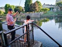 Cerca de Londres el río Támesis y del puente de Putney, un viejo hombre pescaba, una observación del niño imágenes de archivo libres de regalías