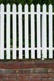 Cerca de madeira branca com base do tijolo fotografia de stock