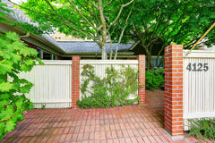 Cerca de madeira com jardim da frente das colunas do tijolo e do assoalho de telha Foto de Stock