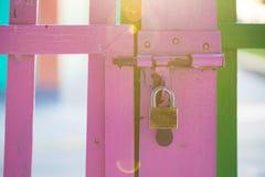 Cerca de madeira da cor cor-de-rosa com o fechamento de segurança com o dom do raio do sol Fotografia de Stock