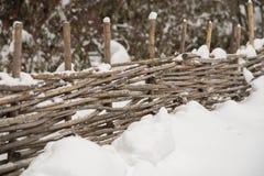 Cerca de madeira dos ramos de árvore cobertos com a neve Imagens de Stock