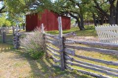 Cerca de madeira e um celeiro vermelho Imagens de Stock