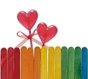 A cerca de madeira em cores do arco-íris e dois pirulitos no coração dão forma Fotografia de Stock