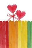 A cerca de madeira em cores do arco-íris e dois pirulitos no coração dão forma Foto de Stock Royalty Free