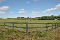 cerca de madeira em torno de um campo do cavalo Fotografia de Stock Royalty Free