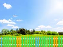 Cerca de madera colorida con la hierba verde en el jardín, cielo azul del claro Fotografía de archivo libre de regalías