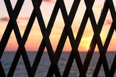 Cerca de madera con la opinión de la puesta del sol Imagenes de archivo