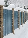 Cerca de madera con las columnas de piedra cubiertas con nieve Fotos de archivo libres de regalías