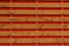 Cerca de madera con los tableros horizontales del fondo rojo imagen de archivo