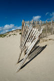 Cerca de madera gastada en la playa arenosa con el cielo azul Fotos de archivo libres de regalías