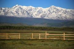 Cerca de madera de los tableros paralelos en las montañas cubiertas por a Imagenes de archivo