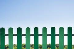 Cerca de madera verde con la hierba y el cielo azul Fotos de archivo