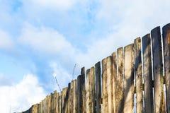 Cerca de madera vieja con la puerta en fondo del cielo Fotos de archivo libres de regalías