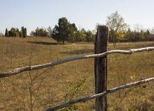 Cerca de madera vieja con un campo en el fondo foto de archivo libre de regalías