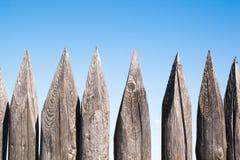 Cerca de madera vieja de la palizada en fondo del cielo azul Foto de archivo libre de regalías