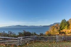 Cerca de madera y hojas de otoño caidas en la hierba, en el foreg Fotos de archivo
