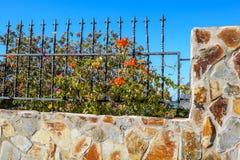 Cerca de piedra hermosa con las barras de hierro y flores hermosas fotografía de archivo
