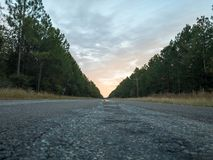 Cerca de puesta del sol a lo largo de una carretera rural sola foto de archivo