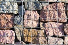 Cerca decorativa feita das rochas atrás dos fios fotografia de stock
