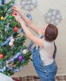 Cerca del árbol la muchacha embarazada en el Año Nuevo Foto de archivo