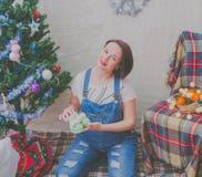 Cerca del árbol la muchacha embarazada en el Año Nuevo Imagen de archivo libre de regalías