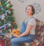 Cerca del árbol la muchacha embarazada en el Año Nuevo Imágenes de archivo libres de regalías
