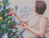 Cerca del árbol la muchacha embarazada en el Año Nuevo Fotografía de archivo libre de regalías