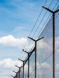 Cerca del alambre de púas bajo fondo del cielo Imagen de archivo libre de regalías