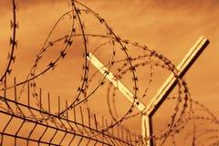 Cerca del alambre de púas de la prisión en la puesta del sol Fotografía de archivo