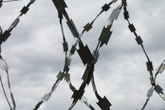 Cerca del alambre de púas y cielo nublado Foto de archivo libre de regalías