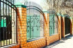 Cerca del ladrillo y del metal con la puerta y puerta de la cerca moderna Ideas del metal del diseño del estilo fotografía de archivo libre de regalías