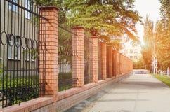 Cerca del ladrillo y del metal con la puerta y puerta del diseño moderno del estilo en el sol poniente Cerca Ideas del metal fotos de archivo