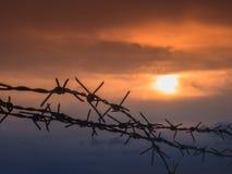 Cerca do arame farpado com o céu crepuscular a sentir silencioso e só e para querer a liberdade Imagens de Stock Royalty Free