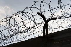 A cerca do arame farpado em torno da prisão mura o céu azul Foto de Stock