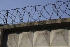Cerca do arame farpado unida em torno das paredes da prisão Imagens de Stock Royalty Free
