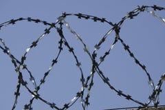 Cerca do arame farpado unida em torno das paredes da prisão Fotografia de Stock